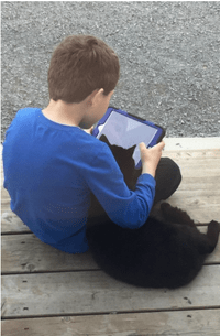 Boy with his black cat watching his Ipad